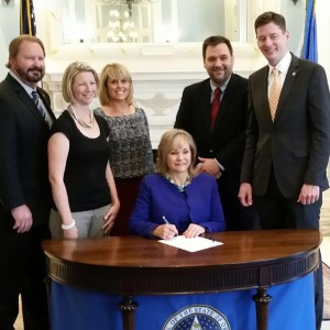 Picture of bill signing for Senate Bill 313, which creates secure online system for accepting voter registration applications. Shown are Senator Randy Bass, Senate Minority Staffer Sarah Taylor, Pam Slater with State Election Board, Governor Mary Fallin, Election Board Secretary Paul Ziriax, Senator David Holt.